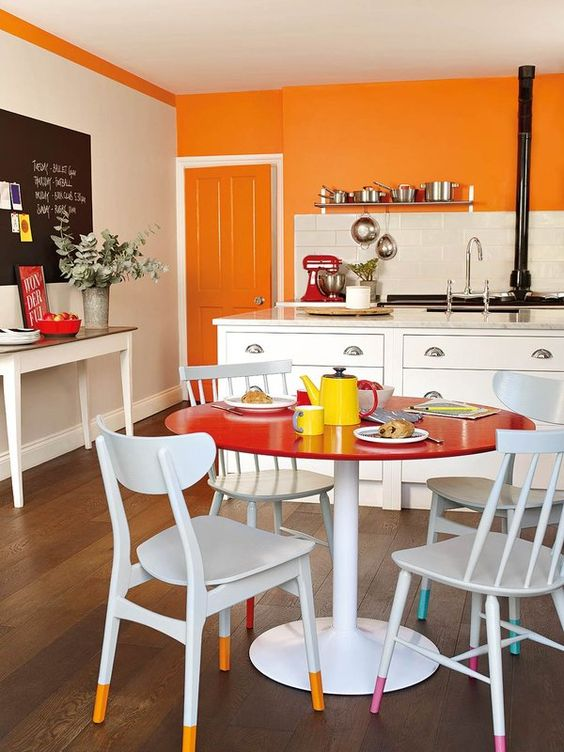 a colorful eat-in kitchen with an orange accent wall, white cabinets, a bright dining space with a round red table and chairs with colorful legs