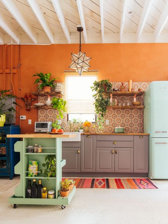 a colorful kitchen with an orange accent wall, a bright mosaic tile backsplash, grey cabinets, a blue fridge and a green cart kitchen island