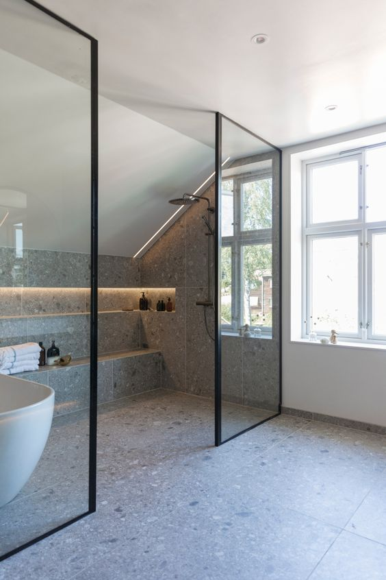a contemporary attic bathroom clad with grey terrazzo tiles, a shower space, a lit up niche for storage, some windows