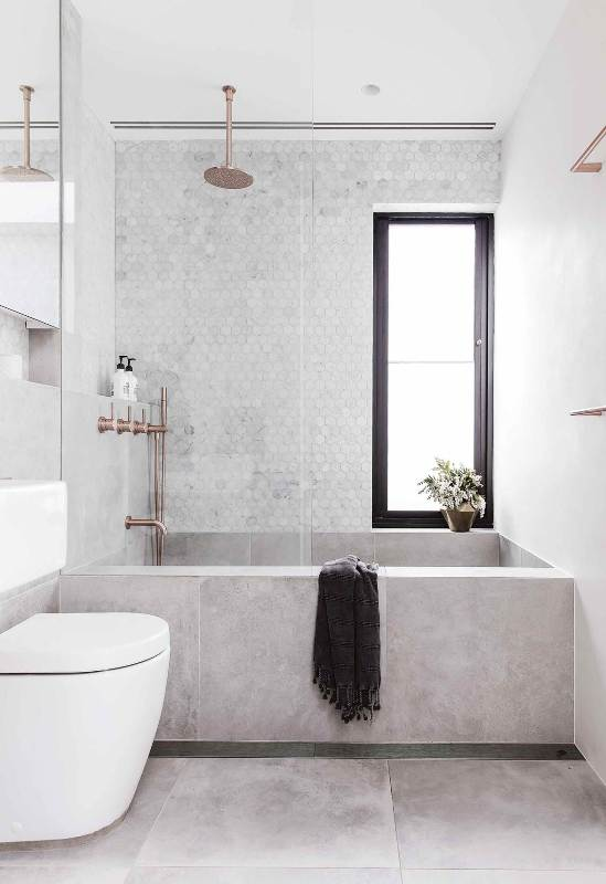 a contemporary bathroom clad with concrete and marble hex tiles, a tub clad with concrete tiles, white appliances and cropped fixtures