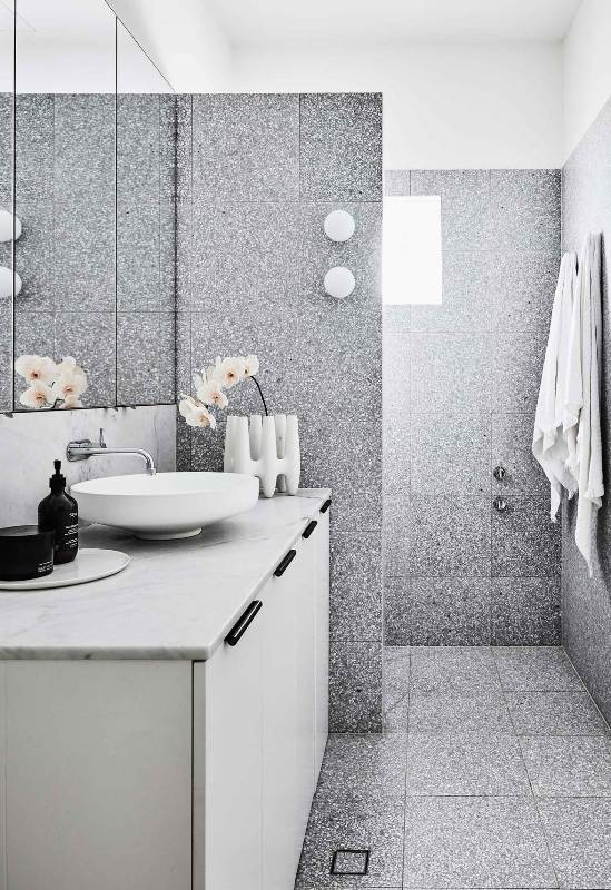a contemporary bathroom clad with grey terrazzo tiles, with a white vanity, a marble countertop, a round sink, a cool vase and orchids