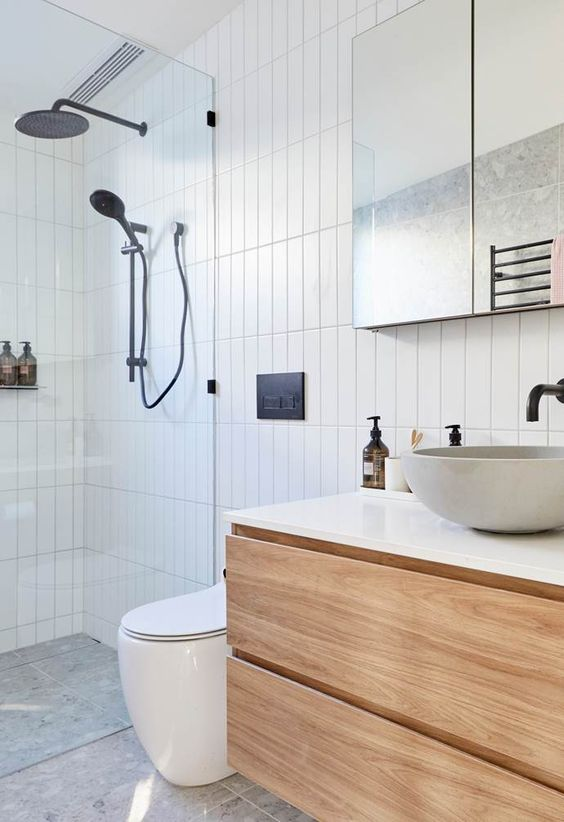 a contemporary bathroom clad with skinny tiles, with a floating vanity, a shower space, a mirror and black fixtures for a contrast