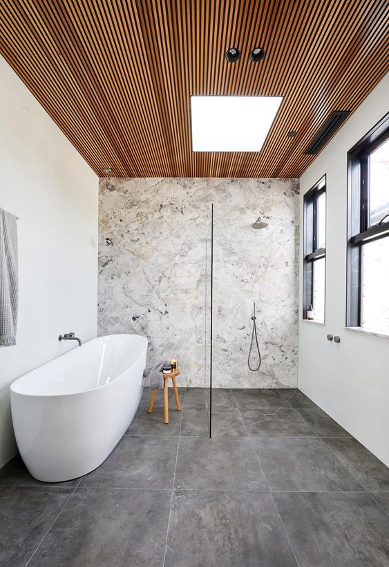 a contemporary bathroom with a stone accent wall, concrete tiles, a wood slab ceiling, neutral fixtures is chic