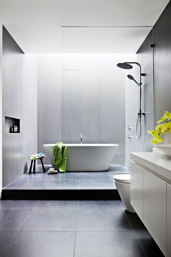 a contemporary bathroom with black and grey large scale tiles, a tub, a floating white vanity, white appliances and neutral fixtures