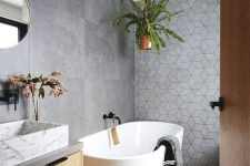 a contemporary bathroom with large scale concrete and geometric tiles, an oval tub, a floating vanity and a white marble sink plus greenery