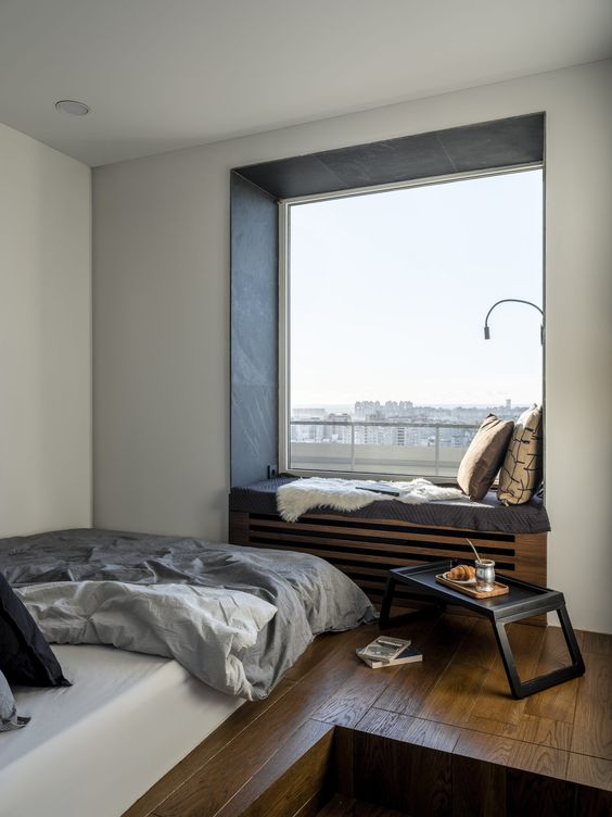 a contemporary bedroom with a large window and a built-in daybed, a bed right on the wall, a small table and a gorgeous view is cool