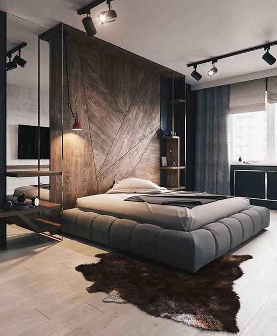 a contemporary bedroom with a wooden accent wall, a grey upholstered bed, spotlights, neutral textiles and an animal skin rug