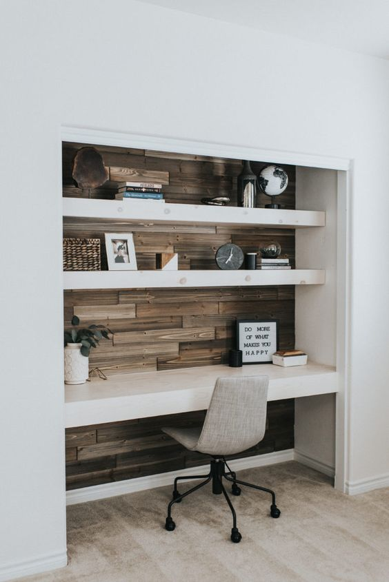 a contemporary built-in home office nook with wood tiles, open shelves and a matching desk, decor and a grey chair