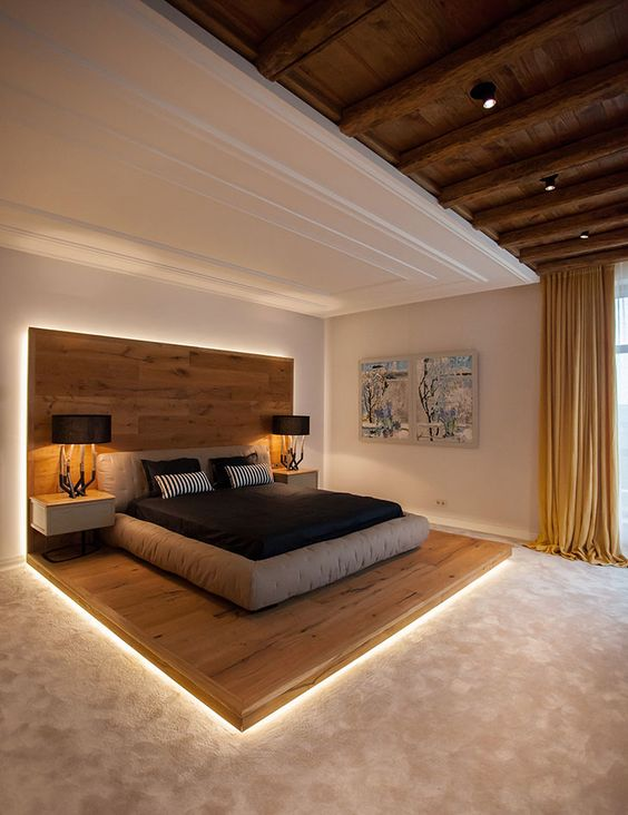 a contemporary chalet-inspired bedroom with a bed on a wooden platform that has an extended headboard, a grey upholstered bed and floating nightstands plus built-in lights