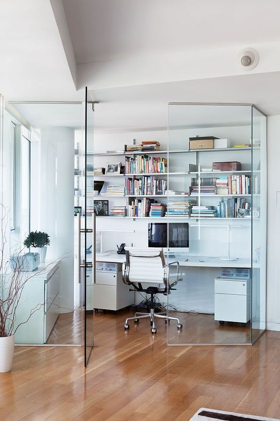 a contemporary glass enclosed home office with open shelves, a desk with storage, a white chair, a sleek white storage unit
