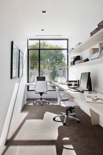 a contemporary home office with a floor to ceiling window, a large corner desk, leather chairs, open shelves and a mini gallery wall