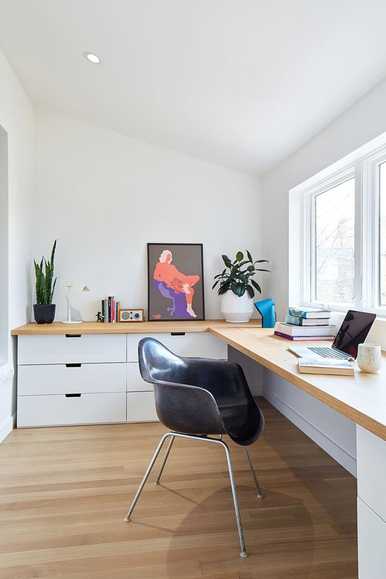 a contemporary home office with a large corner desk with lots of drawers,a small window and potted greenery is cool for working