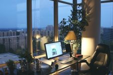a contemporary home office with glazed wall, a black desk and a black leather chair, potted greenery and a tree and lights