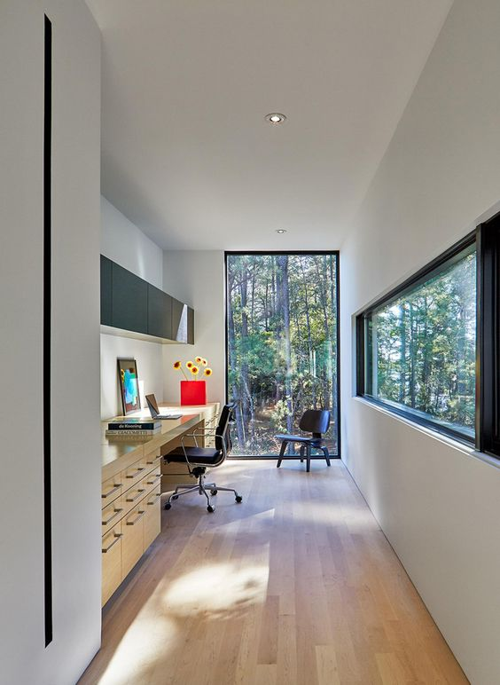 a contemporary home office with windows for amazing views, a large desk with lots of storage compartments, a sleek black storage unit