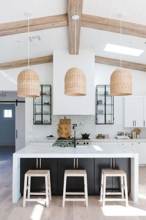 a contemporary kitchen in white, with cabinets with black knobs, a large hood, a black kitchen island with a white countertop and woven pendant lamps