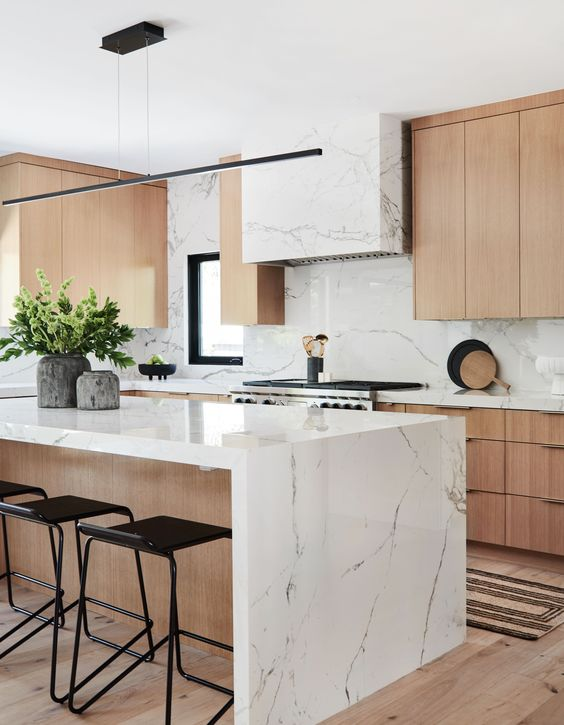 a contemporary kitchen with elegant light-stained cabinets, a white stone hood and countertops plus a bakcsplash and a matching kitchen island