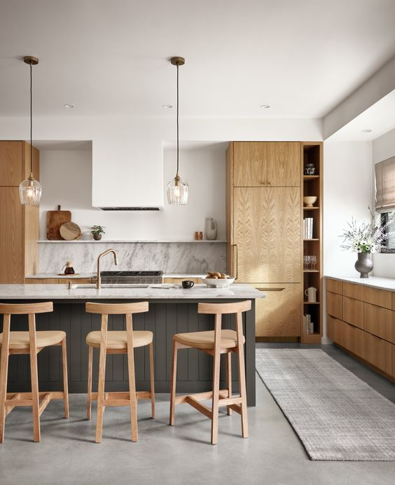 a contemporary kitchen with light stained cabinets, a white hood, a stone backsplash and countertops plus a grey planked kitchen island