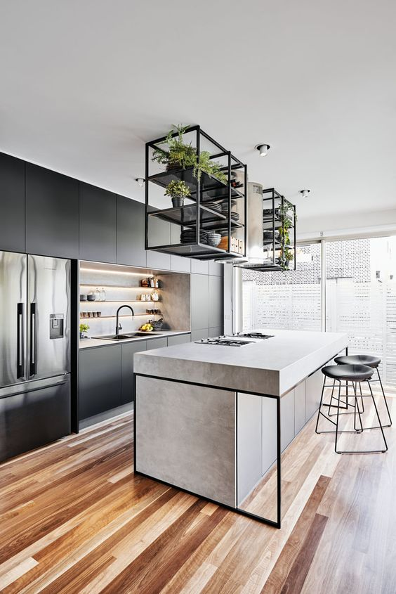 a contemporary kitchen with sleek black cabinets, a concrete kitchen island, black framing, black stools and built-in lights