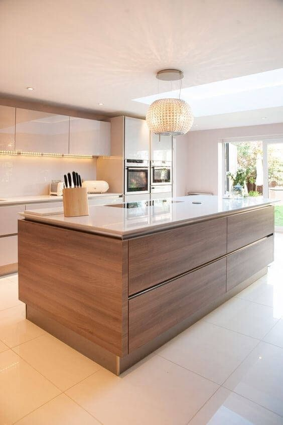 a contemporary kitchen with sleek white cabinets and a rich-stained kitchen island, a sleek white countertop and a backsplash