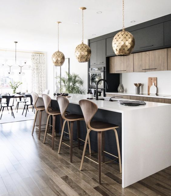 a contemporary kitchen with stained and black cabinets, a black kitchen island, white countertops and a backsplash, gold scale pendant lamps