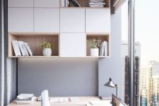 a contemporary light-filled home office in front of a glazed wall, with sleek white and stained furniture, open and closed compartments and a built-in desk