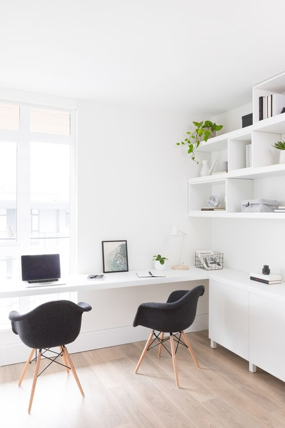 a contemporary light-filled working space with open shelves and sleek cabinets, a built-in desk and black chairs and potted greenery