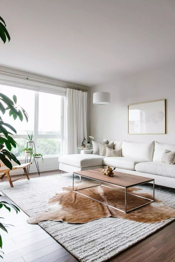 a contemporary living room done in neutrals, with a creamy sectional, layered rugs, a coffee table, potted greenery and creamy textiles