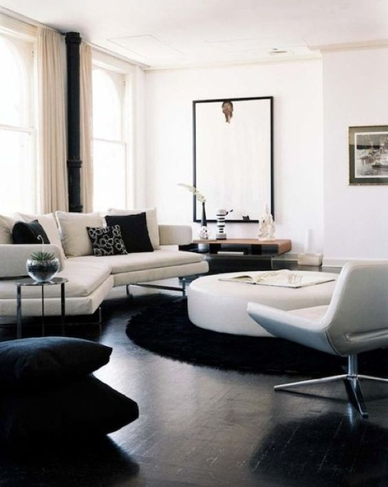 a contemporary living room in black and white, with a black floor, chic white furniture, a round table, a statement artwork and printed pillows