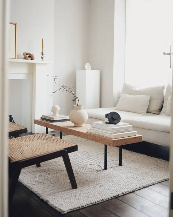 a contemporary living room in creamy shades, a non-working fireplace, a creamy sofa, a cork bench, woven chairs, artworks and a candle
