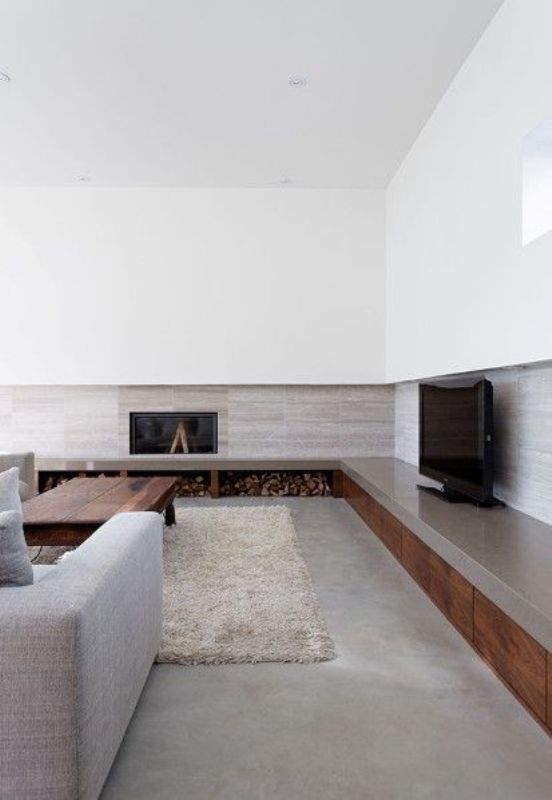 a contemporary living room with a concrete floor, paneled walls, a built-in fireplace and firewood storage, grey seating furniture and a stained table