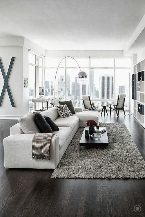 a contemporary living room with a creamy sectional sofa, a grey rug and textiles, printed pillows, a cool floor lamp and a sitting zone by the window