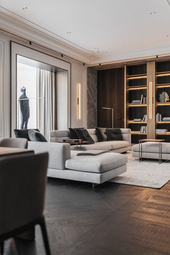 a contemporary living room with built-in shelves, grey seating furniture, built-in lights and a chic dark parquet floor is amazing