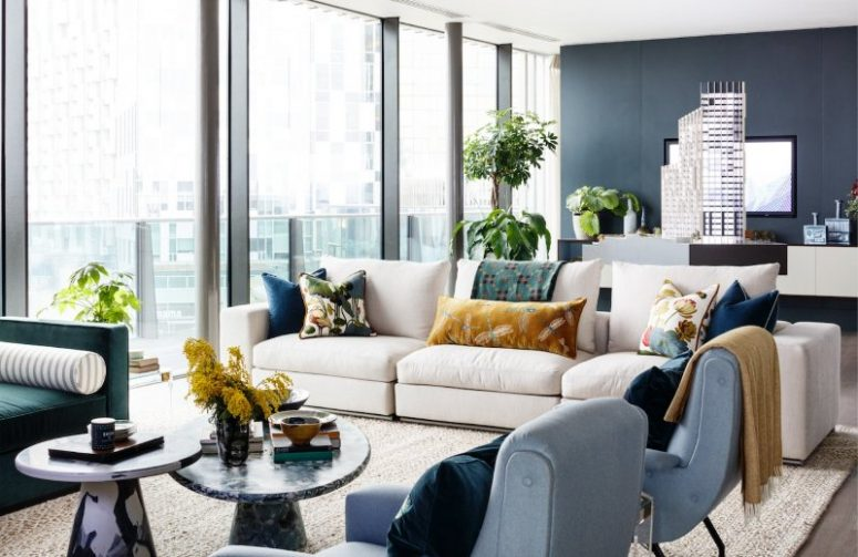 a contemporary living room with splashes of color, a grey wall, a glazed one, muted and jewel tone seating furniture, stone coffee tables and printed pillows