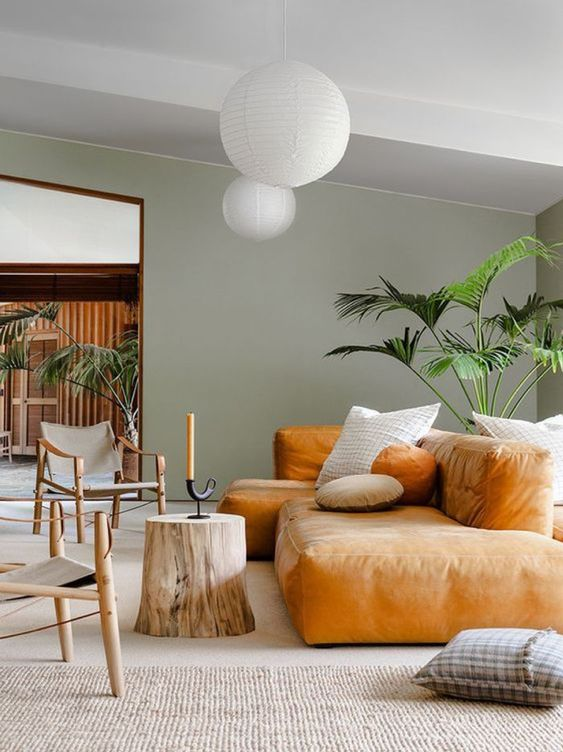 a contemporary living space with an amber-colored low sofa, a tree sutmp, catchy wooden chairs, statement plants and pendant lamps