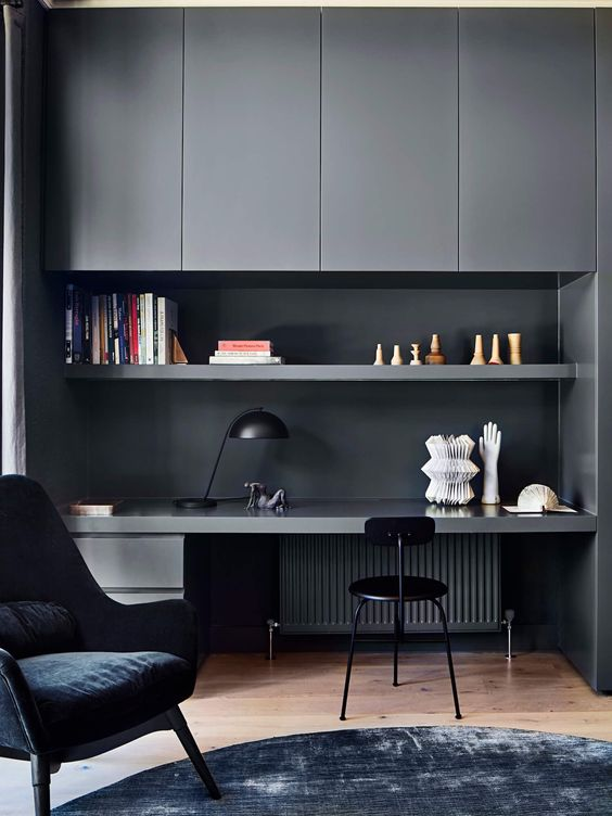 a contemporary moody home office with graphite grey sleek cabinets, an open shelf and a built-in desk, a black chair and a navy one, a black table lamp