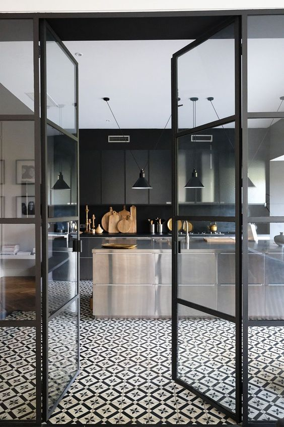a contemporary moody kitchen with ploished metal cabinets, a black backsplash and countertops plus black pendant lamps