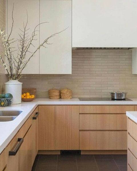 a contemporary neutral kitchen with ivory and light stained cabinets, a brick backsplash, white countertops and black handles is very chic
