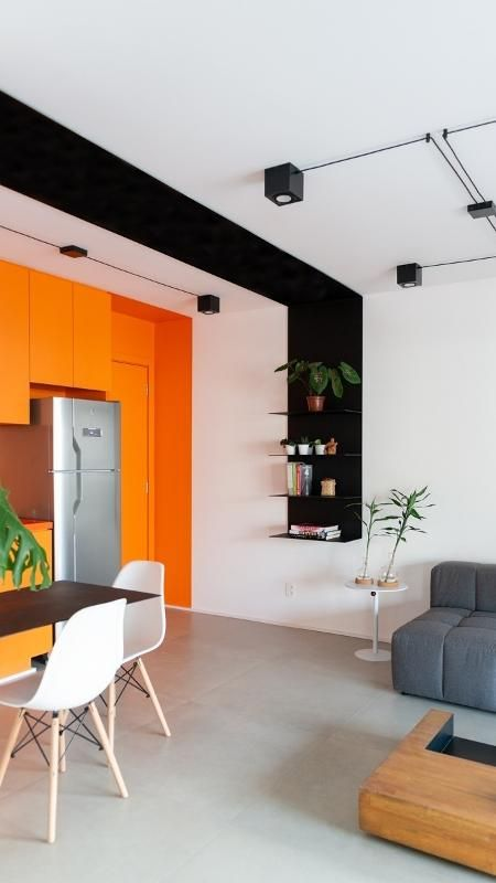 a contemporary open layout with a black and white accent and a whole orange accent wall with orange cabinets and a door is very bold