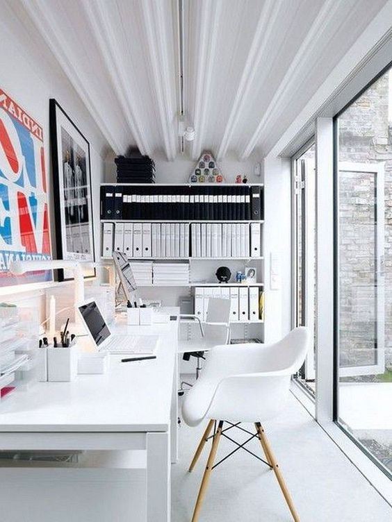 a contemporary shared home office in black and white, with a glazed wall, a double white desk and chairs, cool artworks and open shelves for storage