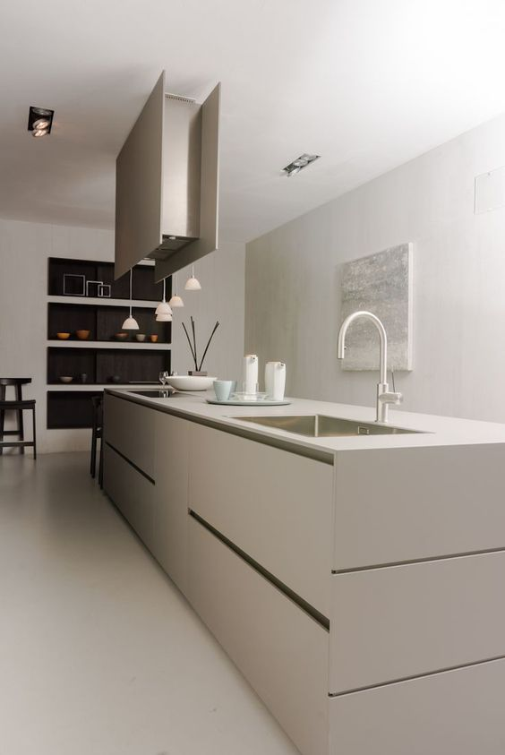 a contemporary to minimalist kitchen done in greige, with a sleek kitchen island, a hood, pendant lamps, niche shelves is amazing
