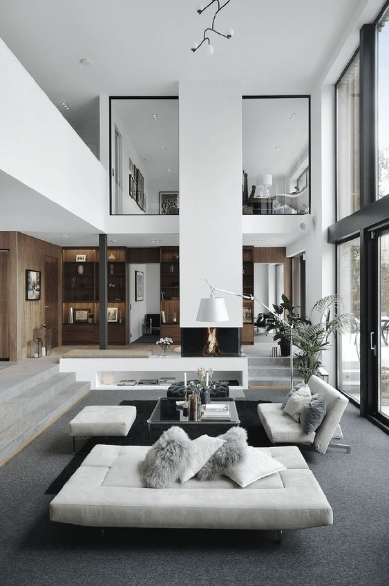 a contemporary to minimalist living room with a built-in fireplace, a glass table, white seating furniture and a potted plant is amazing