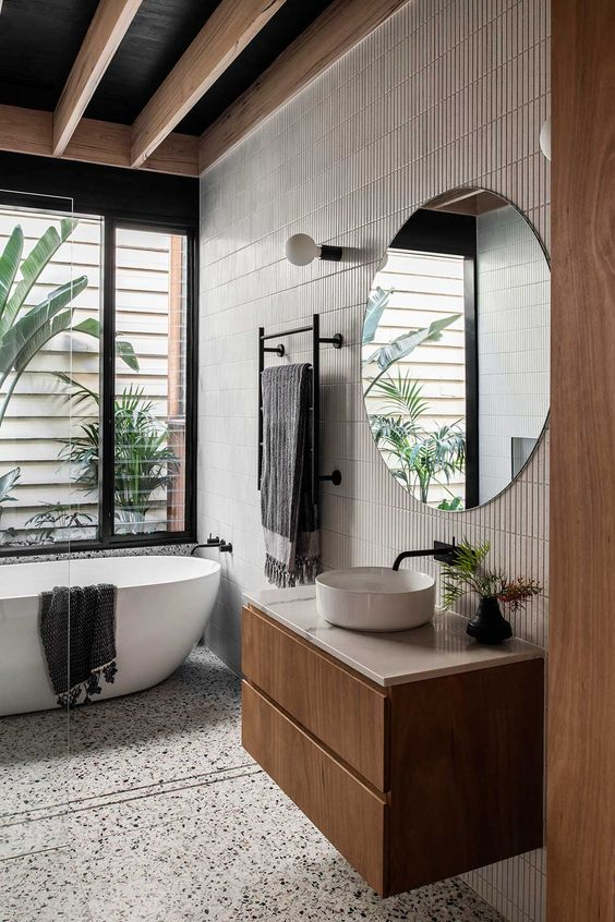 a contemporary tropical bathroom with a white terrazzo floor, an accent wall with skinny tiles, a floating vanity, a round sink and a tub
