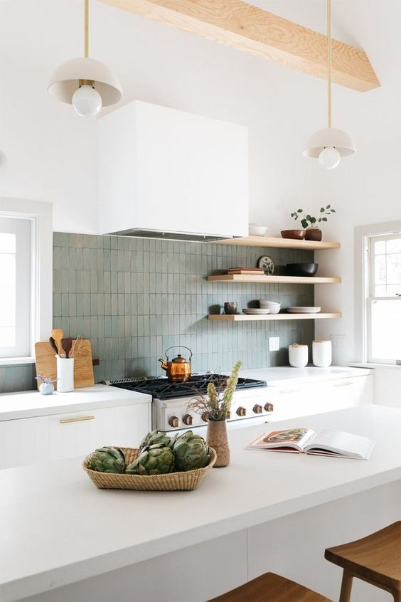 a contemporary white kitchen with elegant cabinets with gold handles, a grey skinny tile backsplash, open shelves and a large kitchen island