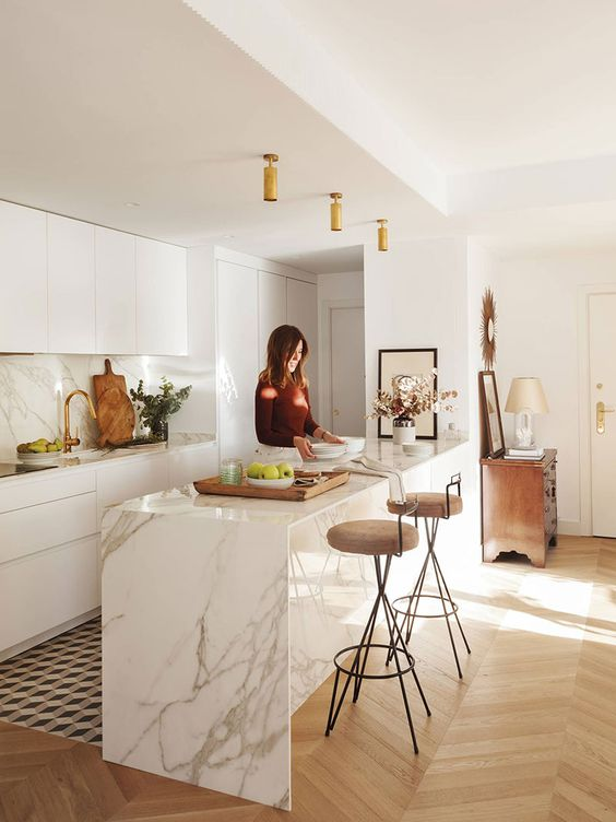 a contemporary white kitchen with sleek cabinets, a white marble kitchen island, matching countertops and a backsplash