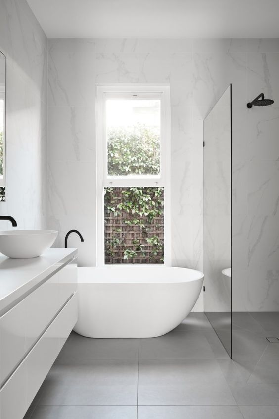 a contemporary to minimalist bathroom with a shower space enclosed in glass, a floating vanity, a tub and black fixtures