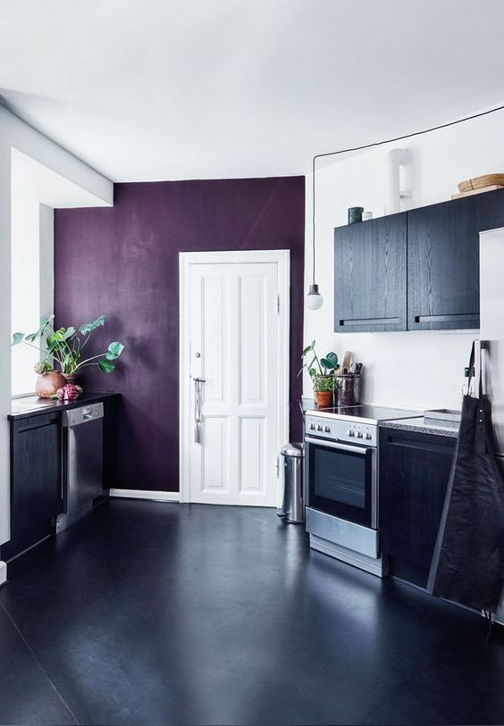 a contrasting black and white kitchen with a deep purple accent wall that adds color and interest to the space and makes it wow