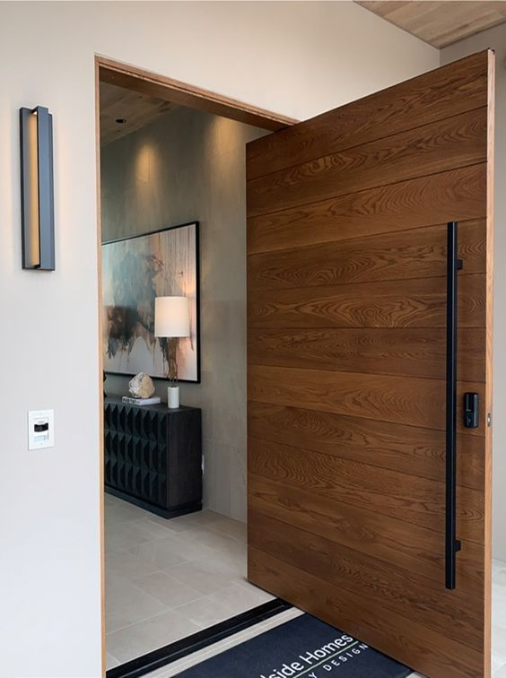 a cool and heavy wood pivot door with a black long handle is a beautiful and lovely idea for a modern entrance