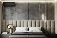 a cool contemporary bedroom with a grey accent wall and a grey upholstered bed with an extended headboard, built-in nightstands and edgy pendant lamps