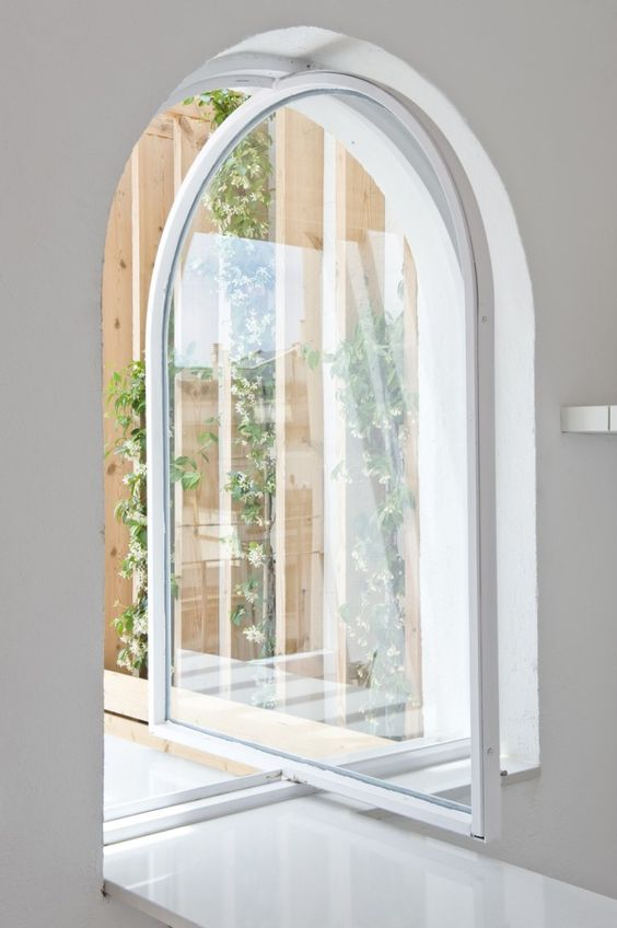 a cool white arched metal frame and glass pivot door that leads to the garden is a gorgeous idea to rock
