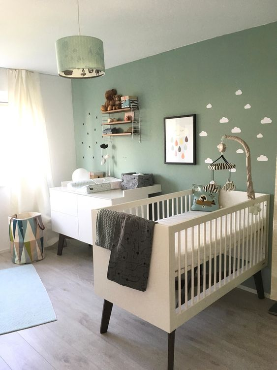 a cozy Nordic nursery with a sage green accent wall, white furniture, a pendant lamp and some shelves plus neutral bedding